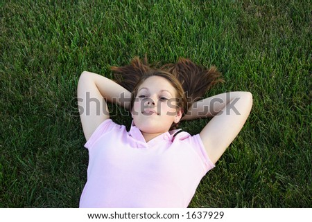 Young woman being silly laying in the grass