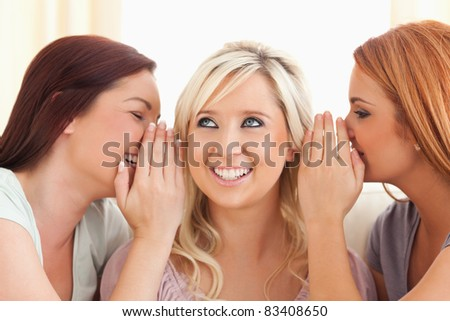 Young woman being told two secrets at a time in a living room