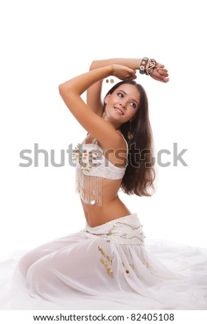 young woman belly dancer in white costume sitting on the floor isolated on white background - stock photo
