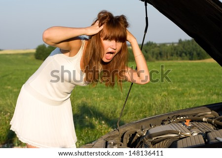 young woman bent over car engine - stock photo