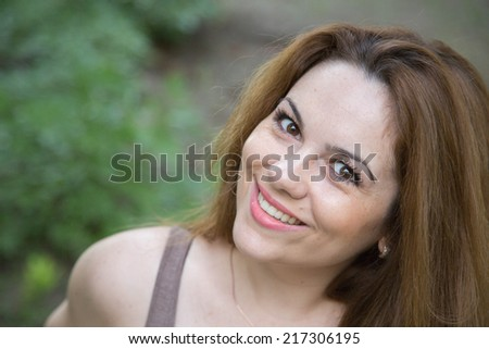 Young woman between twenty-five and thirty years old is smiling in a very charming way