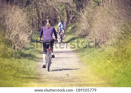 Young woman bicycling in the forest - stock photo
