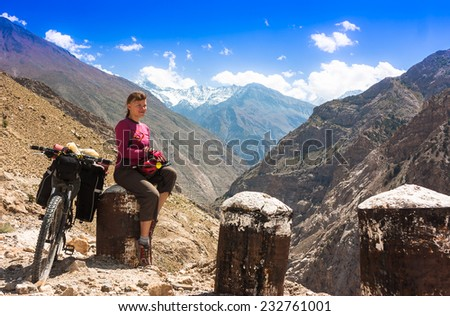 Young woman bicyclist sitting on road in himalayas mountain landscape. Jammu and Kashmir State, North India  - stock photo