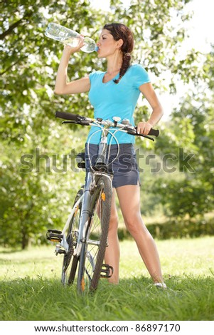 Young woman biker thirsty drinking water - stock photo