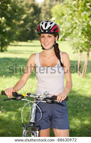 Young woman, biker with her bike - stock photo