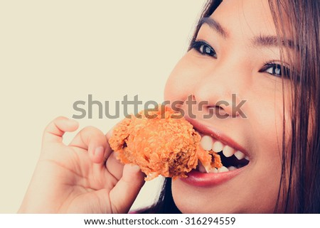 Young woman biting fried chicken, vintage tone - stock photo