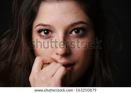 Young woman biting her knuckle