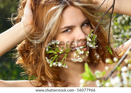 Young woman biting small branch outdoors portrait. - stock photo