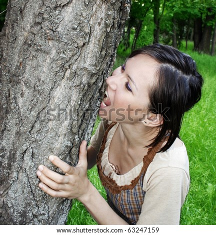 Young woman biting the tree bark - stock photo