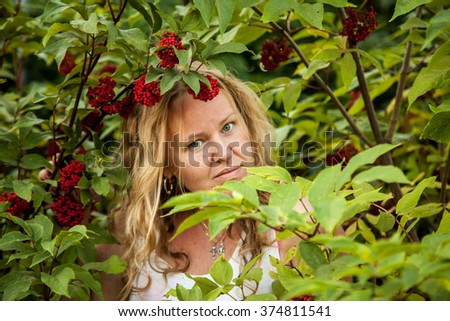 young woman blonde with long hair in the brush mountain ash, viburnum. Green leaves and red berries. Health, natural healing and beauty - stock photo