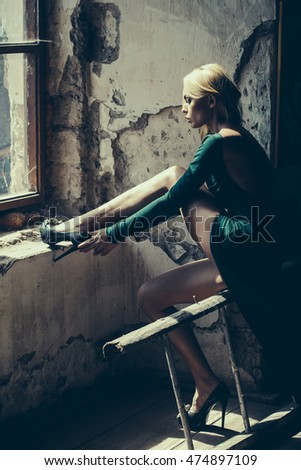 Young woman blonde with splendid legs dressed in sexy green dress with bare back and high-heeled black shoes posing in old room at window indoor