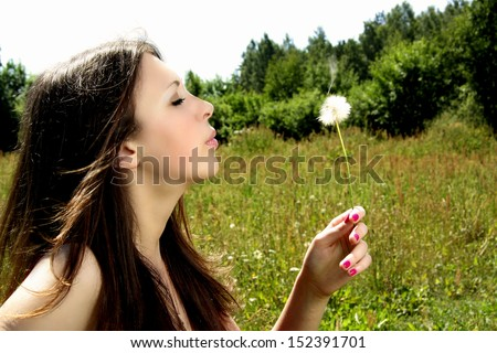 Young woman blowing a dandelion - stock photo