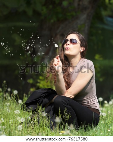 Young woman blowing blowball - stock photo