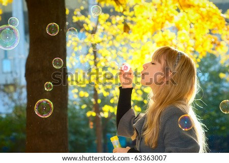 Young Woman Blowing Bubbles on a bright yellow leaves background - stock photo