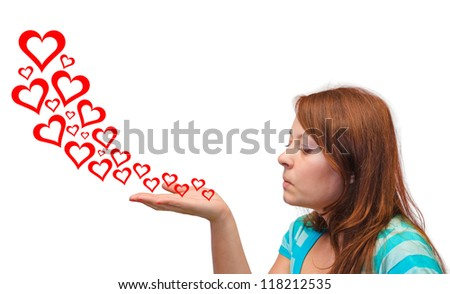 Young woman blowing hearts isolated on white background - stock photo