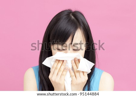 young woman blowing her nose - stock photo