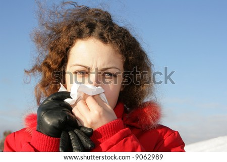 Young woman blowing her nose at tissue - stock photo