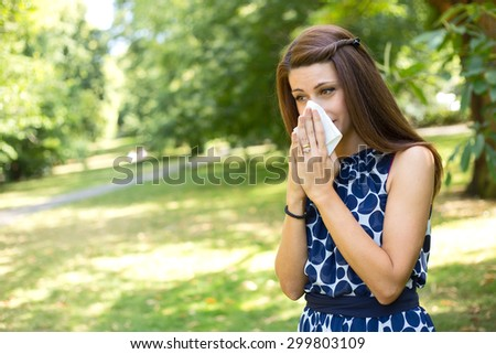 young woman blowing her nose in the park - stock photo