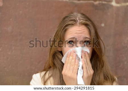 Young woman blowing her nose on a handkerchief conceptual of an illness, flu, cold, allergic rhinitis or hay fever - stock photo