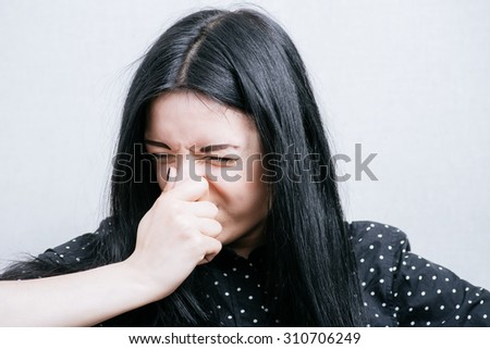 Young woman blowing her nose on gray background - stock photo