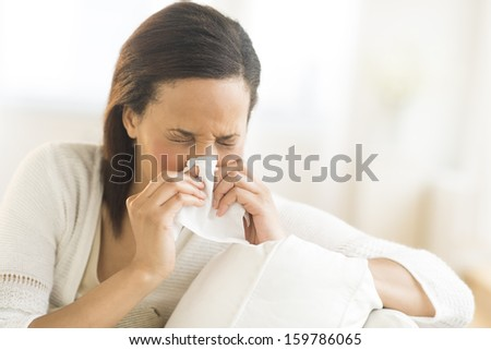Young woman blowing nose - stock photo