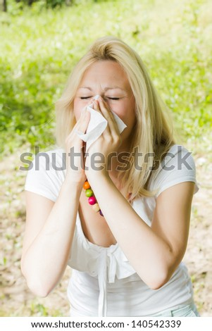 Young woman blowing nose outdoor, pollen allergy, - stock photo