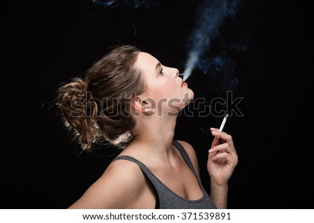 young woman blowing smoke from a cigarette, smoking concept on black background - stock photo
