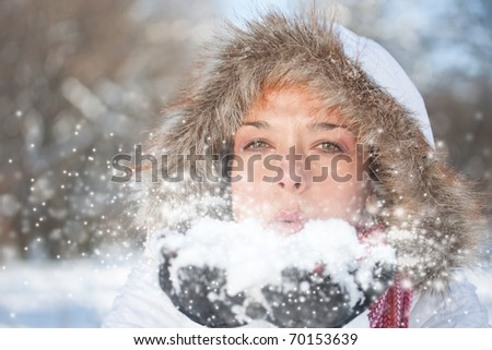 Young woman blowing snow, winter fun - stock photo