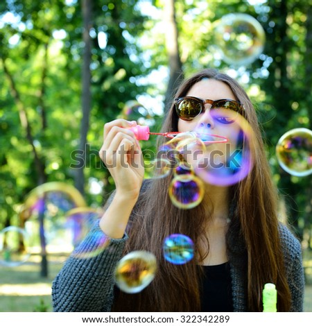 Young woman blowing soap bubbles outdoor in fall park. Image toned and noise added. Soft focus. - stock photo