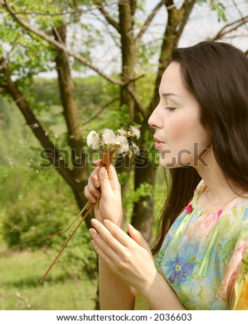 Young woman blows on a dandelion - stock photo