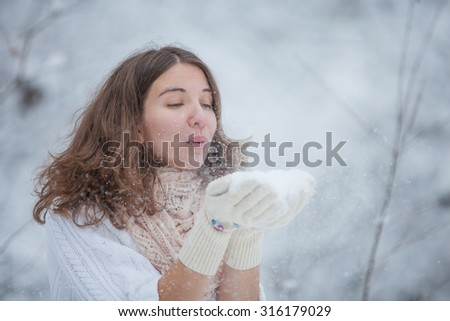 Young woman blows snowflakes in front of her