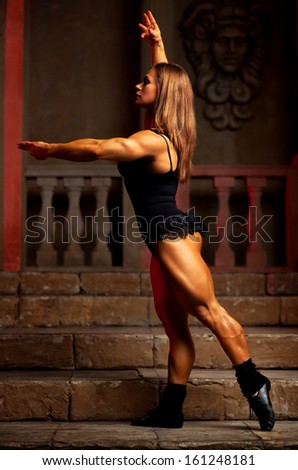 Young woman bodybuilder on ancient background.