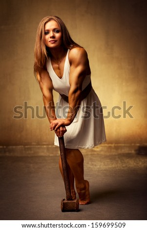 Young woman bodybuilder with hammer. Ancient style.