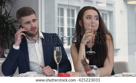 young woman bored to date while her boyfriend having business cell on mobile phone,man busy using their smart phones at the restaurant - stock photo