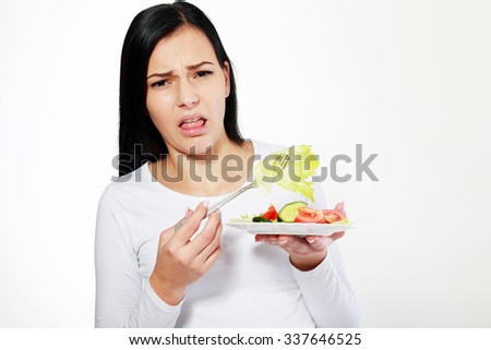 Young woman boring to eat vegetable salad, dieting concept, on white background