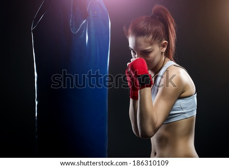 Young woman boxing on a punching bag - stock photo