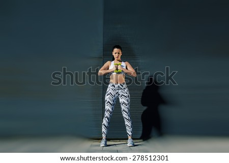 Young woman break the rules and destroy passivity,female in workout gear holding weights with her hands together while training outdoors against black copy space wall for your text message,blur effect - stock photo
