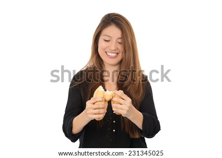 young woman breaking a baguette against a white background - stock photo