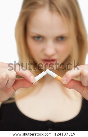 Young woman breaking a cigarette against white background