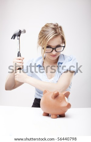Young woman breaking a piggy bank