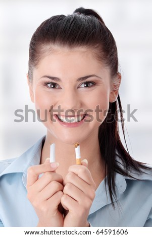 Young woman breaking cigarette