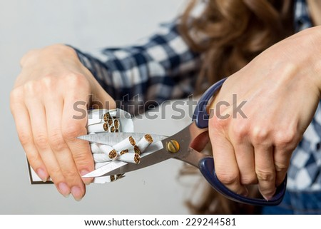 Young woman breaking cigarettes. focus on hand, scissors and cigarettes