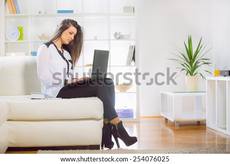 Young woman browsing internet on laptop computer at home on sofa - stock photo