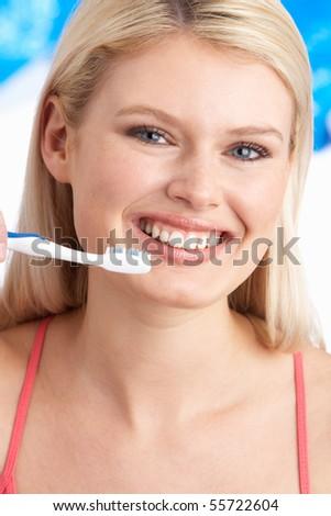 Young Woman Brushing Teeth In Studio - stock photo