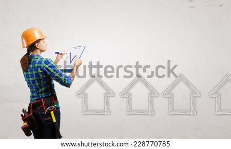 Young woman builder with folder in hand