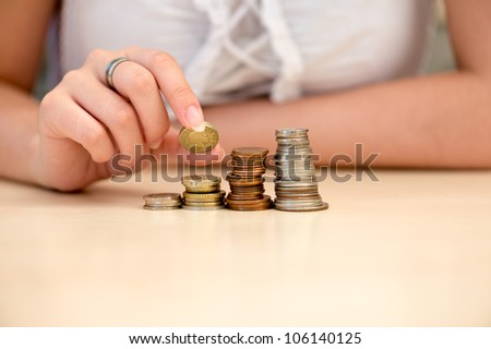 Young woman building coin-stacks like graph - stock photo