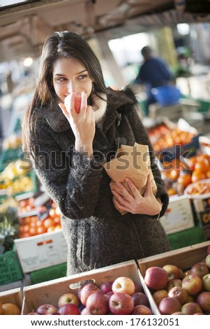 young woman buying apples on a street market - stock photo