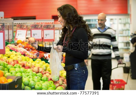 Young woman buying fruits in the supermarket with man in the background - stock photo