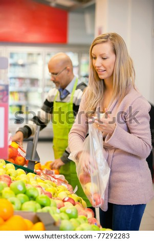 Young woman buying fruits with shop assistant in the background