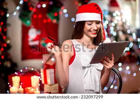 Young woman buying gifts with credit card on Christmas at home - stock photo
